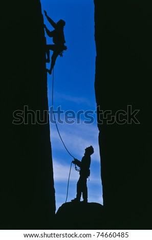 Team of rock climbers struggle to the summit of a steep cliff. - stock photo