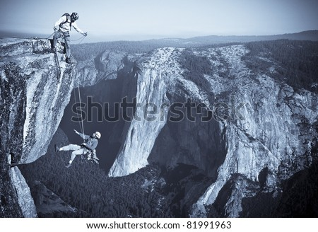 Team of rock climbers struggle up a challenging cliff.