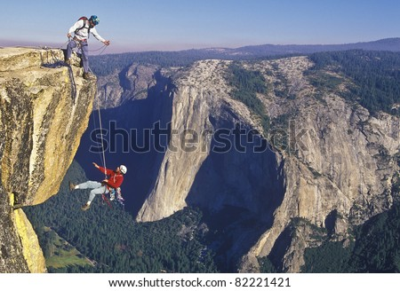 Team of rock climbers struggle up a challenging cliff. - stock photo