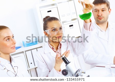 Team of scientists working with liquids in laboratory