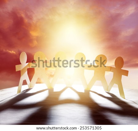 Team of six paper chain people holding hands in front of bright sky   - stock photo
