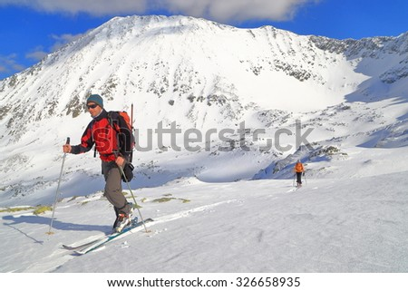 Team of ski mountaineers on snowy mountains during fine winter day - stock photo