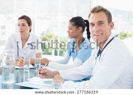 Team of smiling doctors having a meeting in the meeting room - stock photo
