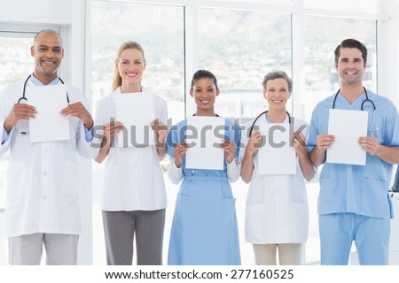 Team of smiling doctors looking at camera and holding paper in medical office - stock photo