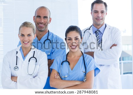 Team of smiling doctors looking at camera with arms crossed in medical office