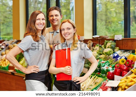 Team of smiling store manager and happy salespeople in a supermarket - stock photo