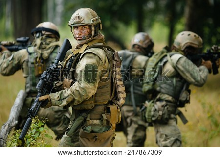 team of soldiers engaged in the exploration of the forest - stock photo