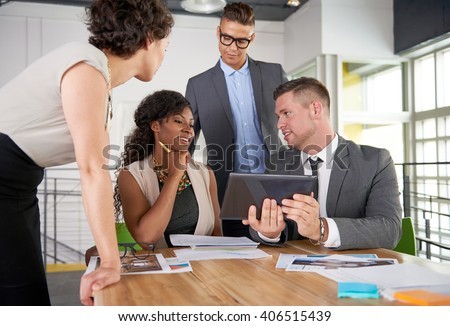 team of successful business people having a meeting in executive sunlit office - stock photo