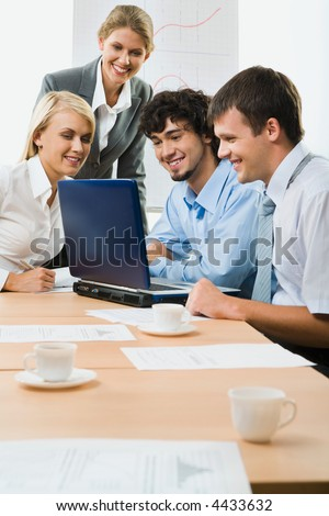 Team of successful business people sitting at the table with laptop, papers and cup on it discussing important questions - stock photo