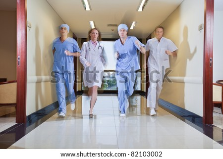 Team of surgeon and nurse running in hallway of hospital - stock photo