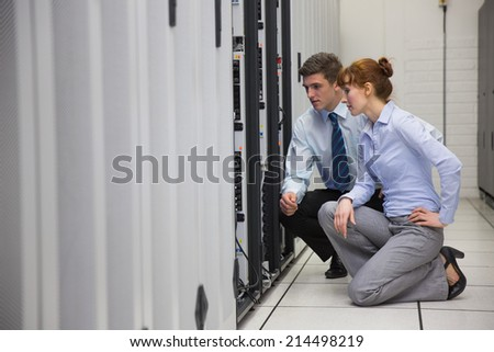 Team of technicians kneeling and looking at servers in large data center - stock photo