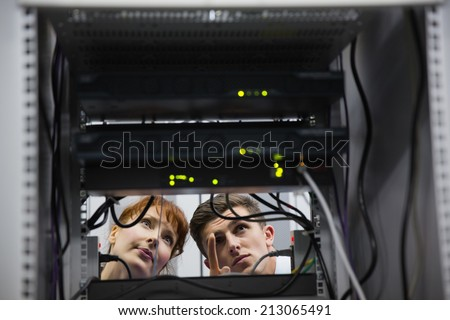 Team of technicians talking and looking at server in large data center - stock photo