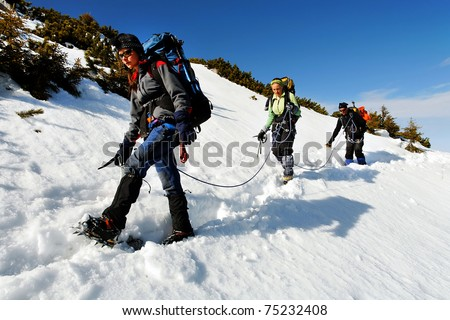 Team of three alpinists descending a mountain - stock photo