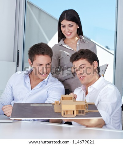 Team of three architects with house model in their office - stock photo