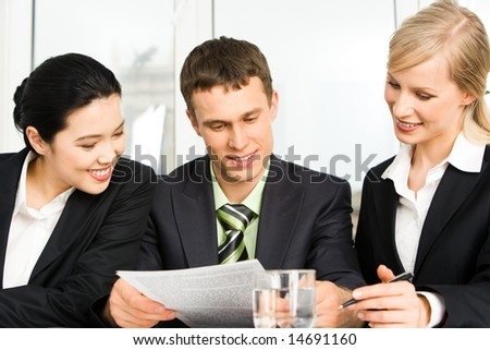 Team of three business people looking at document and brainstorming