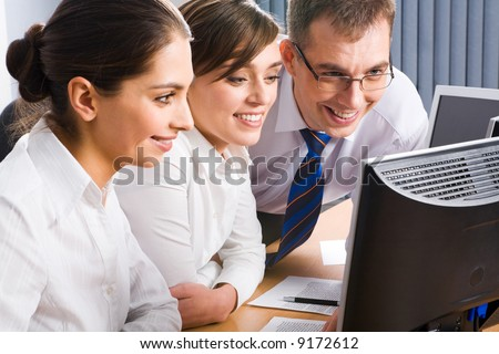 Team of three business people looking at the monitor and discussing some computer work