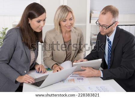 Team of three business people sitting together at desk in a meeting. - stock photo