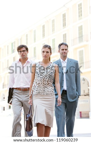 Team of three business people walking together through a classic city square with office buildings in the background during a sunny day.
