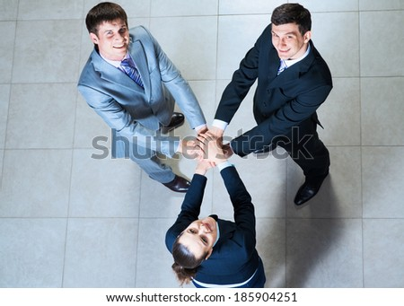 team of three businessmen with folded hands, a symbol of teamwork - stock photo