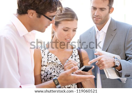 Team of three busy business people gathering around in a casual meeting outdoors, using a digital device to work. - stock photo