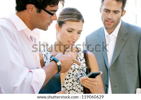 Team of three busy business people gathering around in a casual meeting outdoors, using a digital device to work.