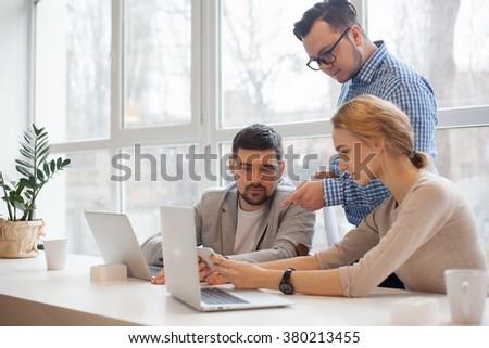 team of three coworkers in stylish studio - stock photo
