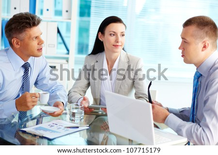 Team of three office workers gathered at one table holding a discussion - stock photo