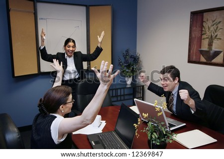 Team of three work colleagues with their arms raised in celebration - stock photo