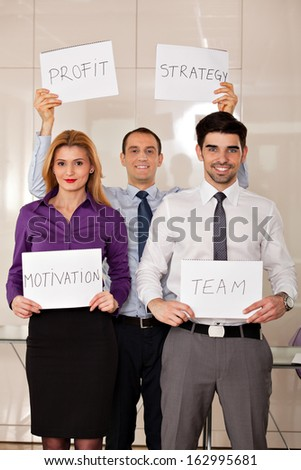 team of three young business people holding four card-boards: strategy, motivation, profit, team - stock photo