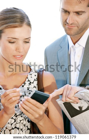 Team of two busy business people gathering around in a casual meeting outdoors, using a digital device to work. - stock photo