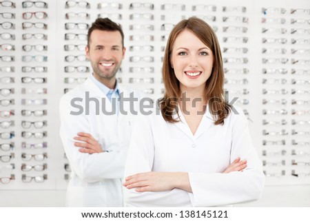 Team of two eye doctors, opticians or optometrists standing in optical shop. - stock photo