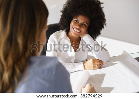 Team of two female architects, sitting at desk in office. The women talk and smile reviewing a building plan. Medium shot - stock photo