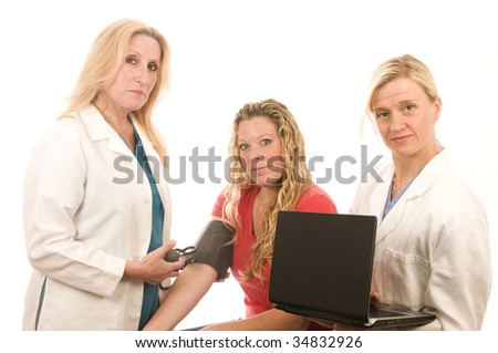 team of two happy and confident female doctors or nurses medical personnel wearing colorful scrubs clothes and lab coats taking blood pressure of pretty blond patient - stock photo