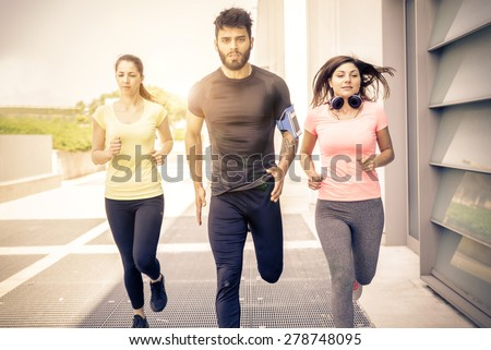 Team of urban runners training - Muscled man and sportive women with sportswear running on the streets  - Friends working out to keep fit and healthy - stock photo