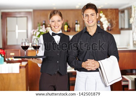 Team of waiter staff with wine glasses in a restaurant - stock photo
