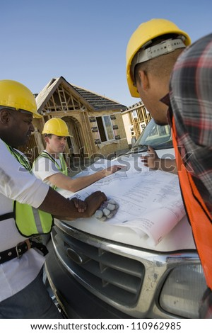 Team of workers discussing over a blueprint - stock photo