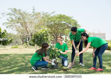 Team of young activists planting tree in the park - stock photo