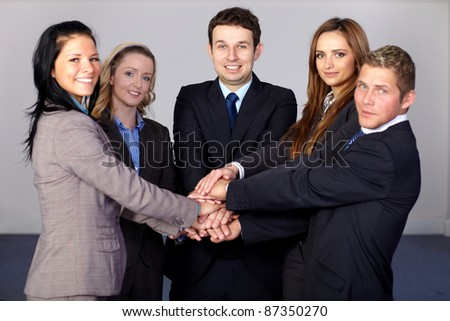Team of 5 young and happy business people, holds their hands together - stock photo