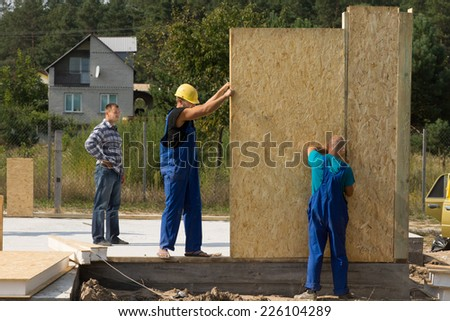 Team of young builders erecting prefabricated wall panels on a building site of a new house - stock photo