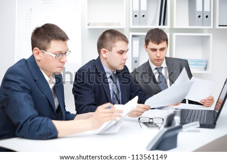 Team of young business men doing some paperwork together at office - stock photo