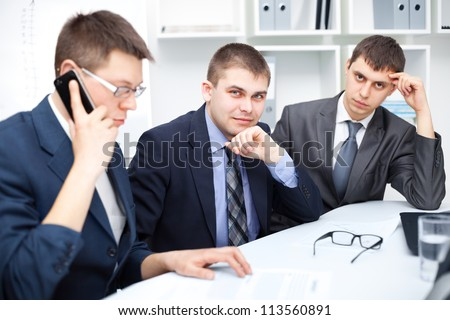 Team of young business men working together at office , one of them talking on a cell phone - stock photo