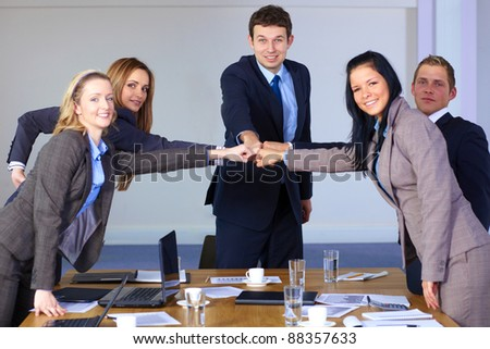 Team of 5 young business people hold their fists together, teamwork and togetherness concept - stock photo