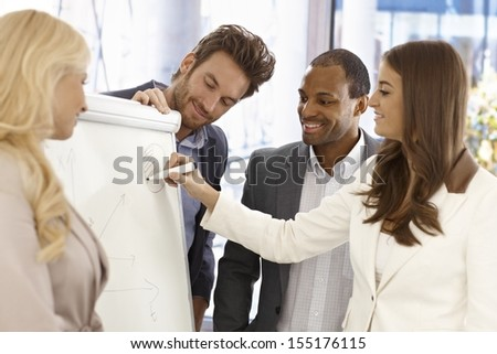 Team of young businesspeople working together, using whiteboard, smiling happy. - stock photo