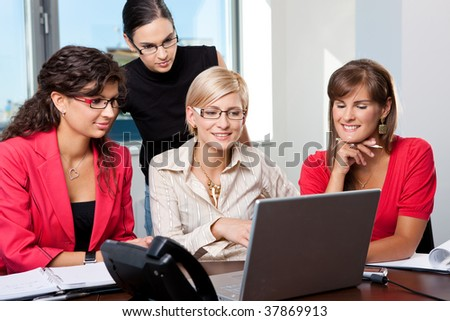 Team of young businesswomen sitting at table in meeting room, using laptop computer, smiling. - stock photo