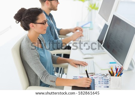 Team of young designers working at their desk in creative office - stock photo