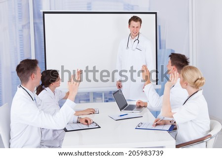 Team of young doctors clapping for colleague after presentation in hospital - stock photo