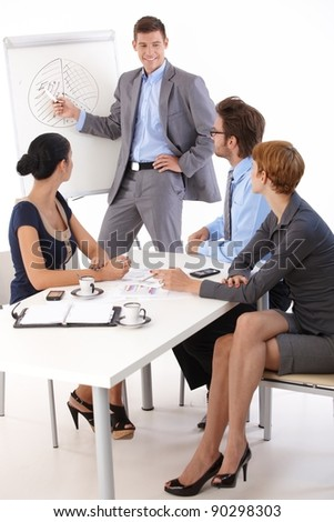 Team of young people working together, businessman presenting, smiling.? - stock photo