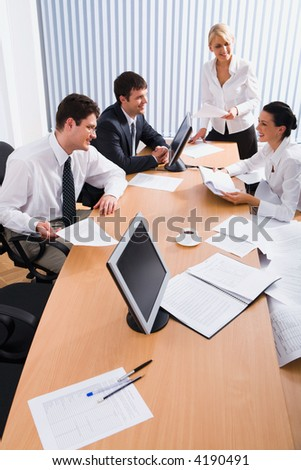 Team of young smiling professionals discuss a plan in the conference room