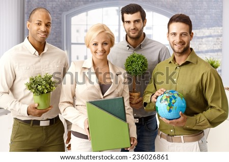 Team portrait of environment friendly businesspeople holding green plants and globe, smiling, looking at camera. - stock photo