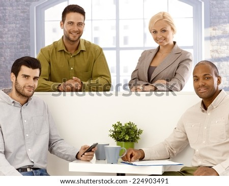Team portrait of happy young businesspeople looking at camera. - stock photo